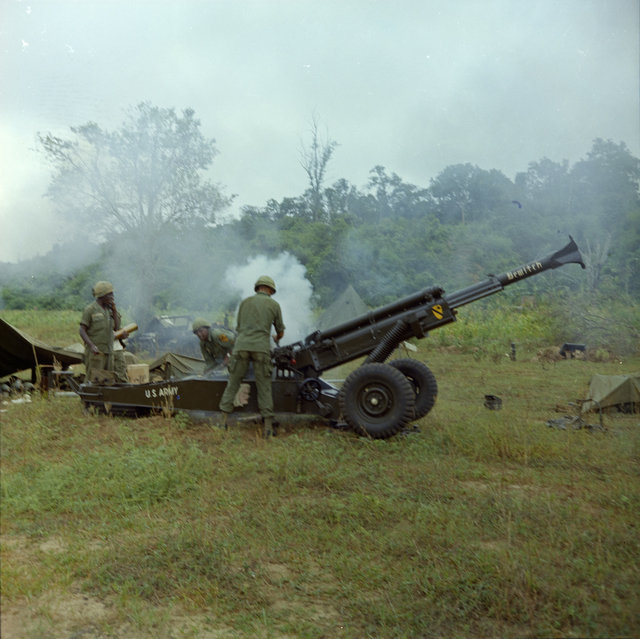 Photograph of a M-102, 105mm Howitzer Firing at Suspected Viet Cong