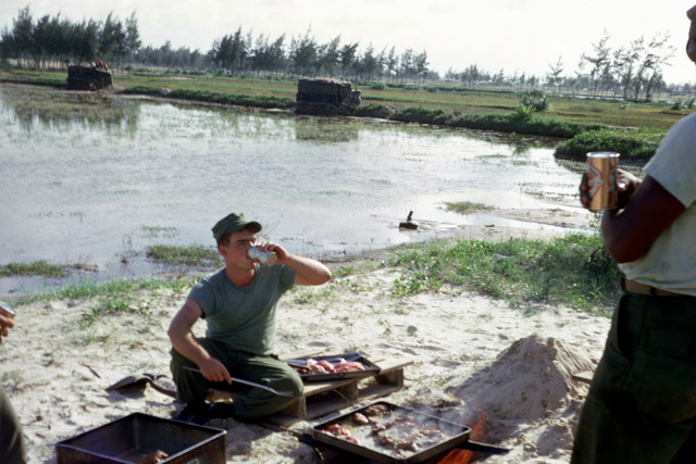 A bulk fuel area cook prepares steak dinners in Cua Viet. Perimeter bunkers are at the edge of the flooded rice paddy in the background