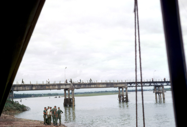 A group of Marines gather at the Dong Ha ramp on the Cam Lo (Cua Viet) River. The bridge in the background carriers Highway 1 over the river