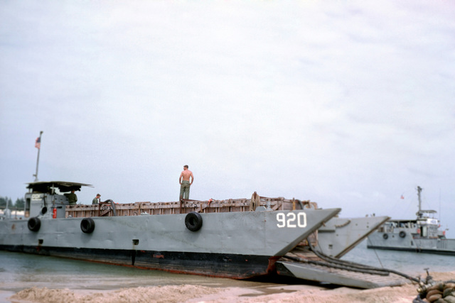 A mechanized landing craft 8 (LCM 8) (Hull No. 920) beached at the Cua Viet Marine bulk fuel unit. Inside the wooden craft in the cargo well is a 10,000-gallon fuel bladder that is used to shuttle fuel from Cua Viet to fuel supply facilities at Dong Ha. Utility landing craft 1498 (LCU 1498) is visible in the background