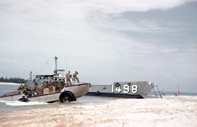 A starboard bow view of utility landing craft 1498 (LCU 1498) beached at Cua Viet. A US Navy lighter, amphibious, resupply cargo vehicle (LARC 5) comes ashore with a group of Marines after a run from Dong Ha