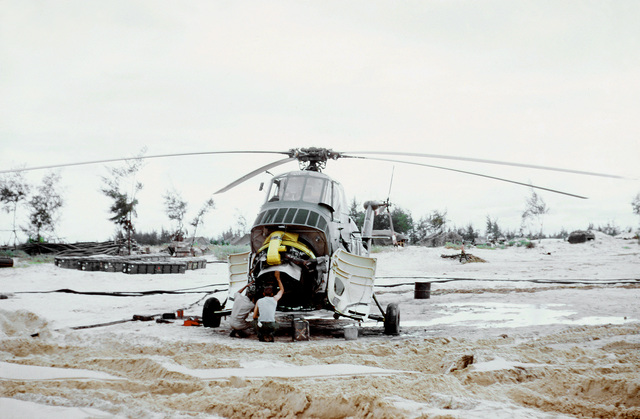 Technicians examine a disabled CH-34 Seahorse helicopter on the beach at Cua Viet