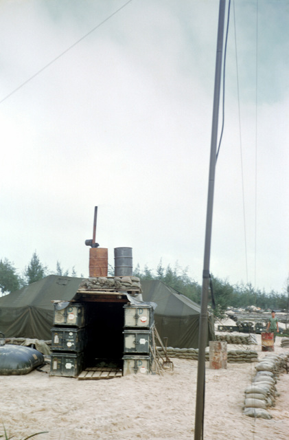 A Marine-built shower unit in the bulk fuel area at Cua Viet. The shower consists of two piped-together 55-gallon drums heated by an immersion heater and placed on top of walls made from stacked tank chests. The drums are fed from the 900-gallon bladder on the ground at left