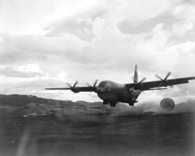 A U.S. Air Force C-130B Hercules aircraft passes low over a drop zone in South Vietnam to deliver a pallet of supplies to ground forces in a forward area. The low altitude parachute extraction system (LAPES) is successfully being used to resupply forward area sites where it is impossible for an aircraft to land