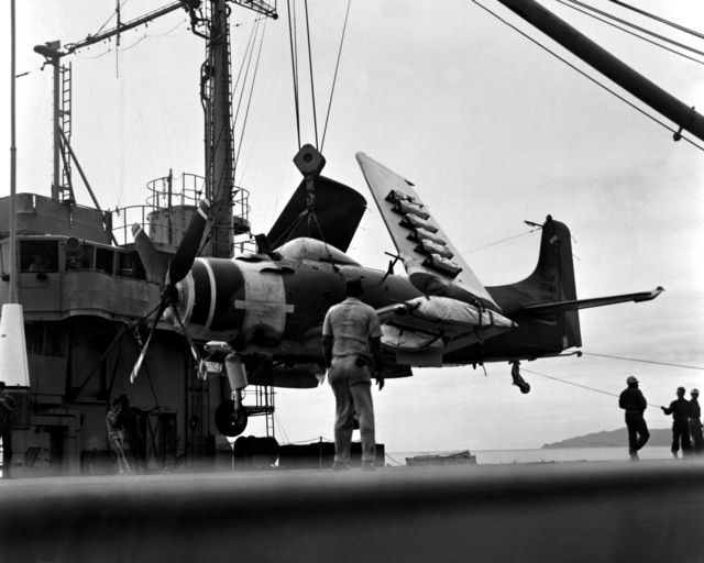 An A-1H Skyraider aircraft is lifted to a barge, the first step in becoming combat ready