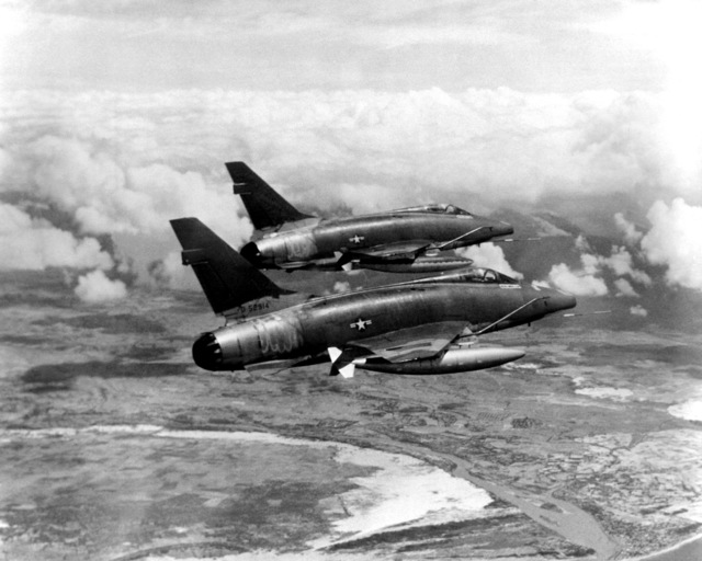 AN air-to-air right rear view of two F-100D Super Sabre aircraft streaking over South Vietnam on their way to an assigned target. The aircraft provides much of the tactical air support to Allied ground forces fighting in Vietnam