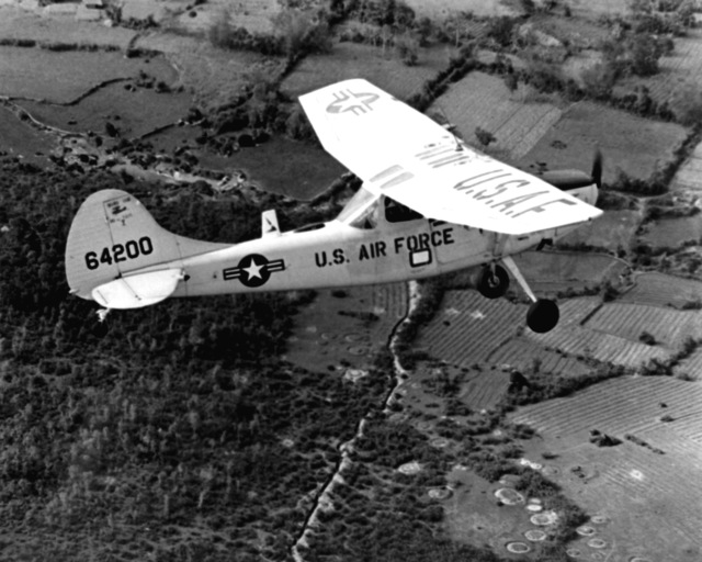 AN air-to-air right side view of a U.S. Air Force 0-1E Bird Dog aircraft. The aircraft is used as a forward air control aircraft throughout South Vietnam. The forward air controller (FAC) spots suspected enemy strongholds and fires smoke rockets to mark the target for strike aircraft. Following a strike the FAC assesses bomb damage
