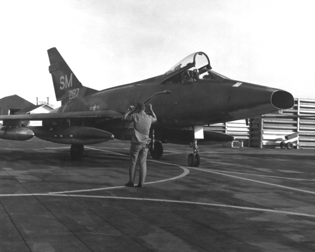 SGT. Robert D. Gray guides a 31st Tactical Fighter Wing F-100 Super Sabre aircraft into its fortified parking place, following a close air support mission over South Vietnam. Wing pilots flew 23,069 sorties since deploying to Vietnam one year ago