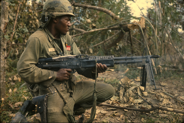 Photograph of Private Milton L. Cook Firing His M-60 Machine Gun into an Area Where a Viet Cong Sniper was Spotted