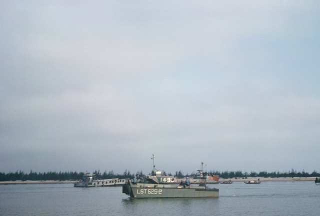 A landing craft, vehicle and personnel (LCVP) from the tank landing ship USS CAROLINE COUNTY (LST 525) underway on the Cua Viet River. In the background is utility landing craft 1498 (LCU 1498) and a mechanized landing craft 8 (LCM 8)