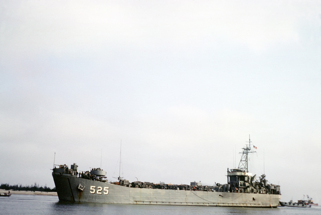 A port bow view of the tank landing ship USS CAROLINE COUNTY (LST-525) on the Cua Viet River. The ship is loaded with cargo trucks. Caroline County is the first LST to dock at Cua Viet