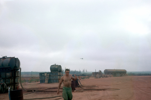 A Marine works in the Dong Ha fuel supply facility. Behind him are 750-gallon gasoline and diesel fuel tanks mounted on top of tank chests to provide gravity feed for the dispensing nozzles