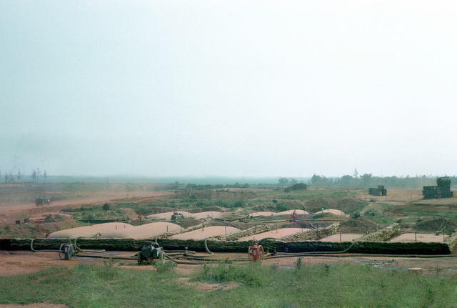 A view of 10,000-gallon fuel bladders in the Dong Ha fuel supply facility. The elevated tank on the right is a 750-gallon fuel mounted on top of tank chests to provide gravity feed for the dispensing nozzles. A 350-gallon-per-minue fuel pump is in the foreground