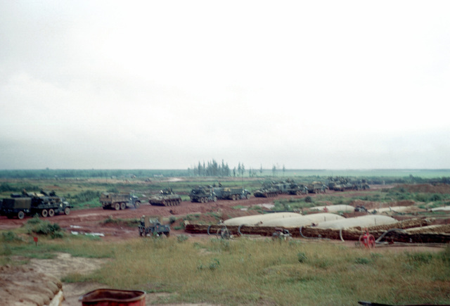 A convoy of trucks and tracked vehicles assembles at the Dong Ha fuel supply facility. Sandbags protect the 10,000-gallon fuel bladders