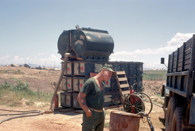 A Marine works in the Dong Ha fuel supply facility. Behind him is a 750-gallon fuel tank mounted on top of tank chests to provide gravity feed for the dispensing nozzles