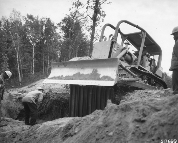 Photograph of Lydick Lake Corpsmen Driving Steel Retaining Wall Along Tramway System Channel Above Knutson Dam