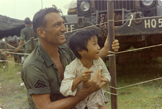 Photograph of Staff Sergeant Hugh L. Maple Playing with a Vietnamese Child