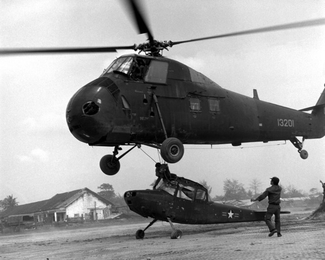 A ground crew member hooks an O-1 Bird Dog aircraft to a Vietnamese Air Force H-34 Choctaw helicopter, hovering overhead