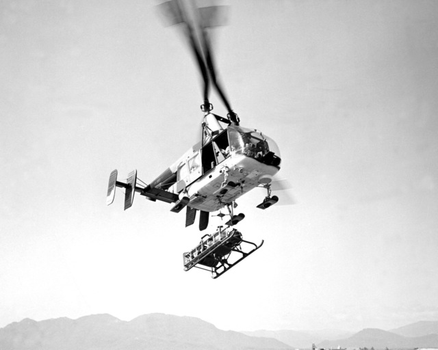 A right underside view of an HH-43B Huskie helicopter lifting a fire suppression kit to a fire battle site. The aircraft is assigned to Detachment 8, 38th Aerospace Rescue and Recovery Squadron