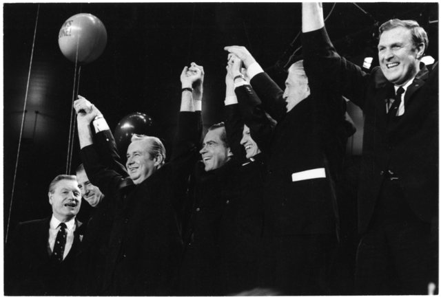 "Nelson Rockefeller, Spiro Agnew, Richard Nixon, and George Romney clasp hands in the air. A balloon reading ""Nixon's the One"" is visible"