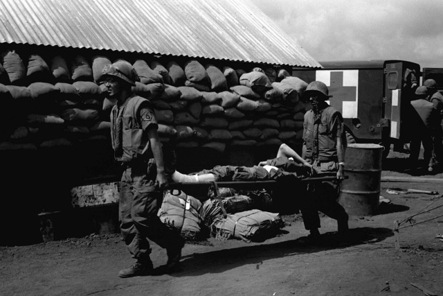 U.S. Air Force medical personnel, on detached duty from Da Nang Air Base, move a Marine casualty from the aid station at embattled Khe Sanh to a waiting C-130 Hercules aircraft for the flight to medical facilities at the base. Wounded personnel can be transported from the field to completely equipped hospitals in less than an hour