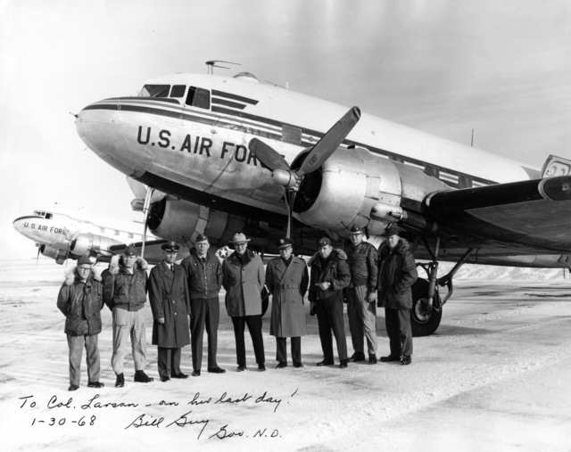 """U.S. Air Force personnel assigned to the 119th Fighter Wing""""Happy Hooligans"""", North Dakota Air National Guard, pose for a photo with North Dakota Governor William Guy after a particularly harrowing flight in which an in-flight mechanical problem nearly resulted in catastrophe as pilots and crew prevented the C-47 Dakota/Skytrain aircraft from having to make a crash landing in 1968. (A3604) (U.S. Air Force PHOTO) (Released)"""