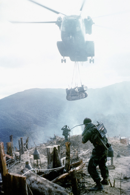 A CH-53 Sea Stallion helicopter airlifts a bulldozer into a mountain-top fire support base construction site. The CH-53 is being guided in by members of a 3rd Marine Division construction team
