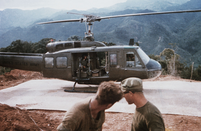 A UH-1 Iroquois helicopter rests on a recently installed landing mat at a mountain-top fire support base. The base is under construction by members of the 3rd Marine Division