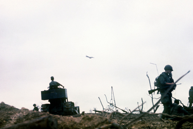 An F-4 Phantom II aircraft passes overhead as a bulldozer clears underbrush from the site of a mountain-top support base. The base is under construction by members of the 3rd Marine Division