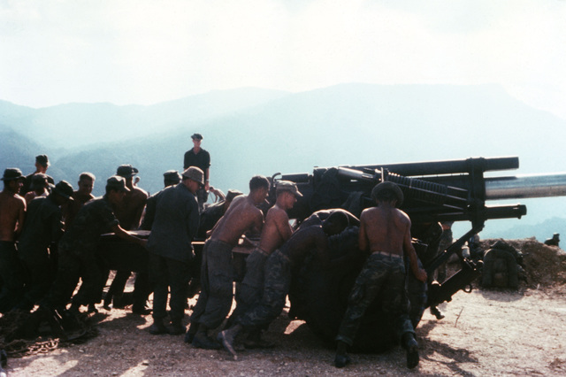 Members of the 3rd Marine Division move an M114 155 mm howitzer into position during construction of a mountain-top fire support base