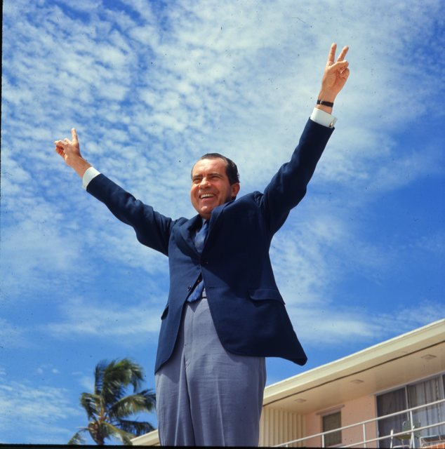 Richard Nixon gestures a double victory sign with his hands and arms extended
