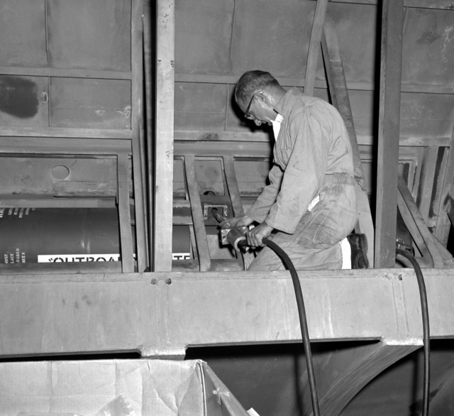 A man works to install a submarine emergency communication transmitter (SEC) buoy Mark 9 Mod O outside the pressure hull and inside the other hull of a simulated submarine hull section during testing at the Naval Ordnance Laboratory. When put into fleet use the SECT will be released and act as a surface marker if and when the ship is sunk