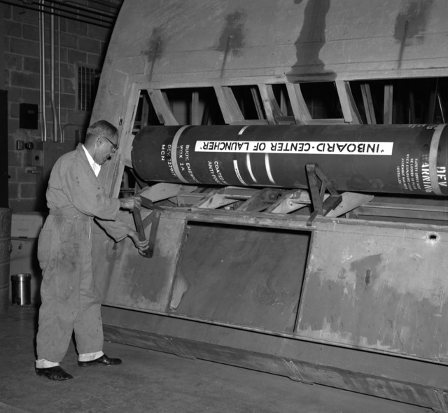 A submarine emergency communication transmitter (SECT) buoy Mark 9 Mod O is loaded aboard a simulated submarine hull section during testing at the Naval Ordnance Laboratory. When put into fleet use the SECT, which will ride outside the submarine's pressure hull and inside the submarine's outer hull, will be released and act as a surface marker if and when the ship is sunk