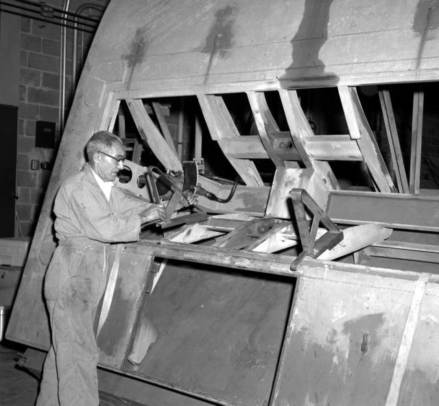 A worker places a chock aboard a simulated submarine hull section prior to the loading of a submarine emergency communication transmitter (SECT) buoy Mark 9 Mod O during testing at the Naval Ordnance Laboratory. When put into fleet use the SECT, which will ride outside the submarine's pressure hull and inside the submarine's outer hull, will be released and act as a surface marker if and when the ship is sunk