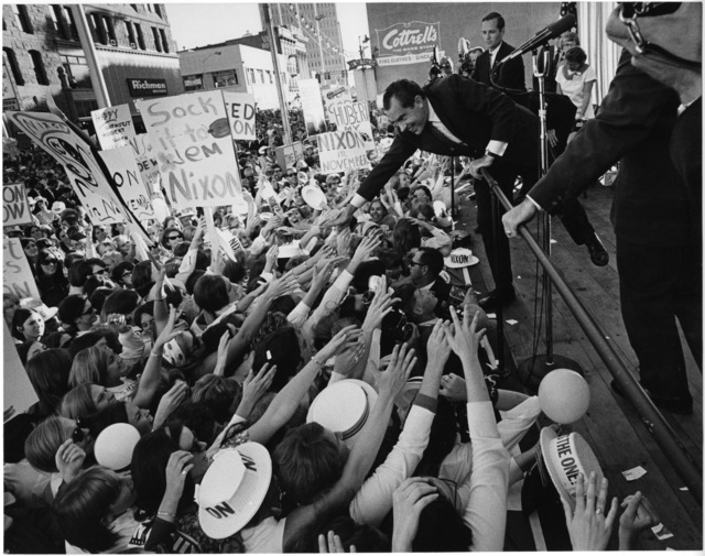 "Presidential candidate Richard Nixon leans to shake hands with a crowd at a campaign event. An attendee holds a ""Sock It To Em"" sign"