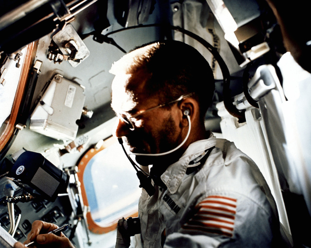 Astronaut Walter Cunningham, Apollo 7 lunar module pilot, writes with a space pen while performing flight tasks on the ninth day of the Apollo 7 mission. A 70 mm Hasselbald camera film magazine floats just above Cunningham's right hand in the zero gravity environment of the spacecraft