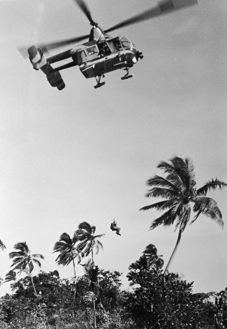 An HH-43 Pedro (Huskie) helicopter is used to rescue a downed airman from an enemy infested jungle in Southeast Asia