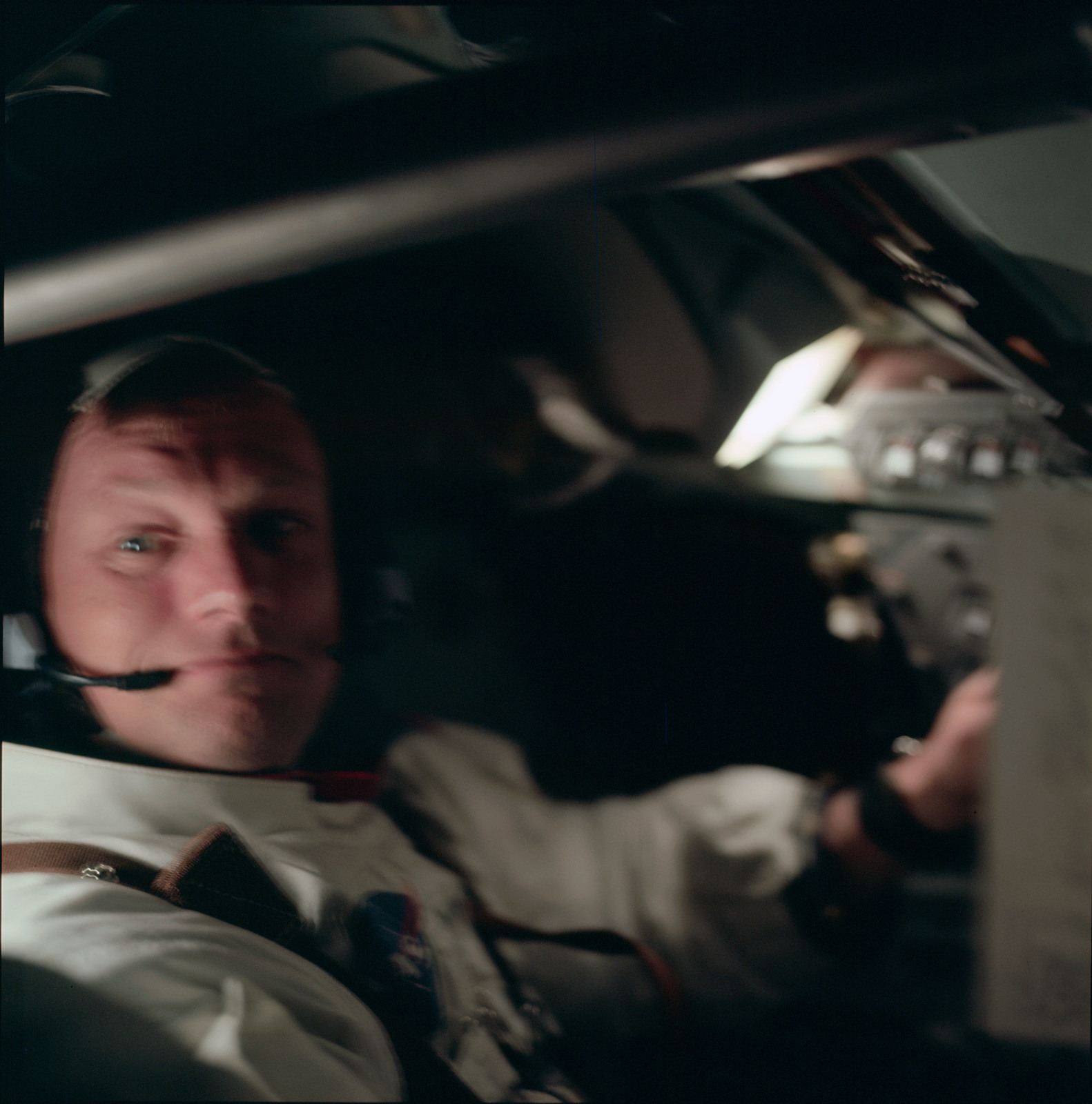 AS11-36-5291 - Apollo 11 - Apollo 11 Mission image - Spacecraft interior with astronaut Neil A. Armstrong looking at camera