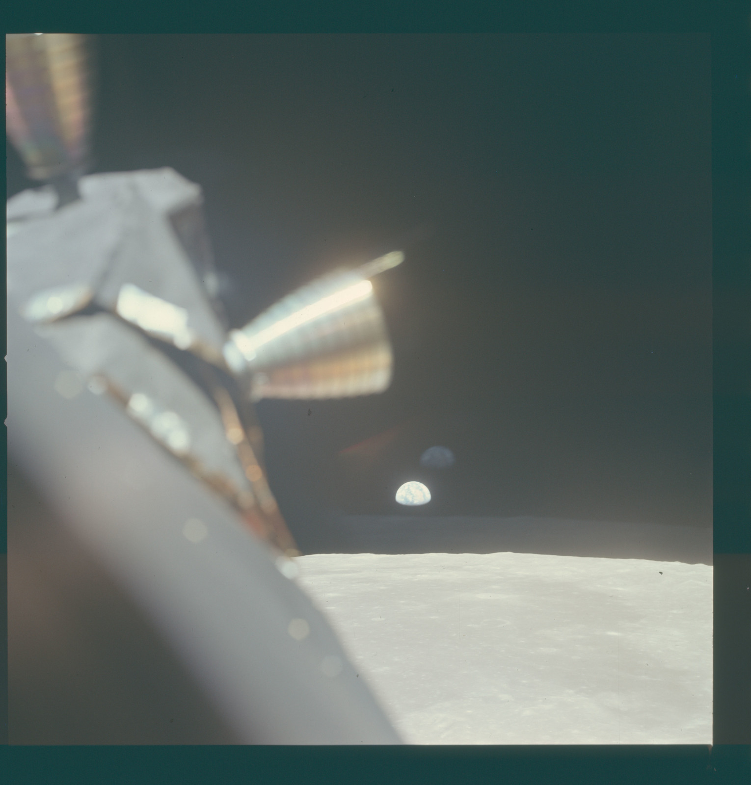 AS11-37-5441 - Apollo 11 - Apollo 11 Mission image - View of Moon, with Earth visible over the horizon