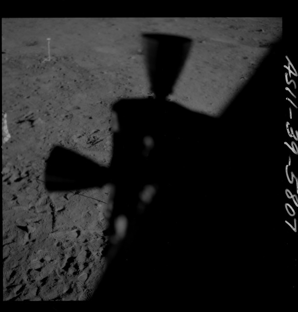 AS11-39-5807 - Apollo 11 - Apollo 11 Mission image - Shadow of Lunar Module thruster and U.S. flag on lunar surface