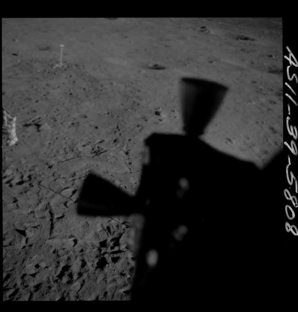 AS11-39-5808 - Apollo 11 - Apollo 11 Mission image - Shadow of Lunar Module thrusters and U.S. flag on lunar surface