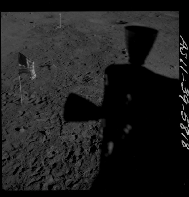 AS11-39-5818 - Apollo 11 - Apollo 11 Mission image - Shadow of LM thrusters and U.S. flag visible on lunar surface