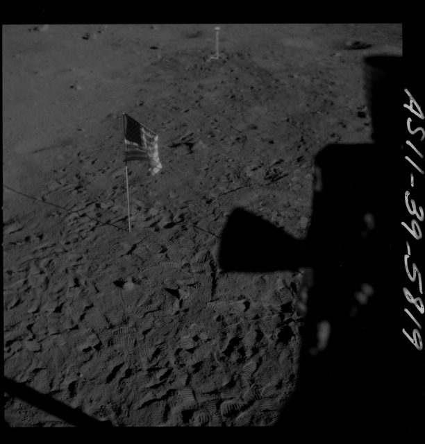 AS11-39-5819 - Apollo 11 - Apollo 11 Mission image - Shadow of LM thrusters and U.S. flag visible on lunar surface