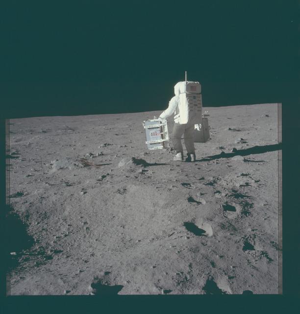 AS11-40-5943 - Apollo 11 - Apollo 11 Mission image - Astronaut Edwin Aldrin carries experiments to deployment area
