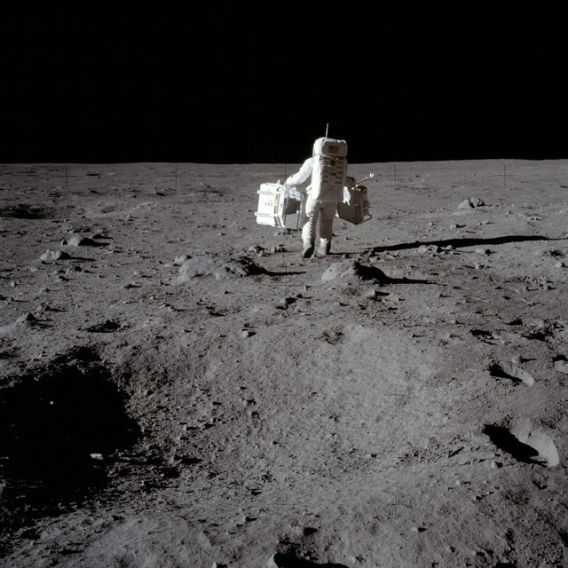 AS11-40-5944 - Apollo 11 - Apollo 11 Mission image - Astronaut Edwin Aldrin carries experiments to deployment area