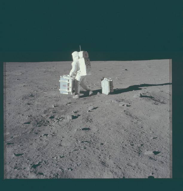 AS11-40-5945 - Apollo 11 - Apollo 11 Mission image - Astronaut Edwin Aldrin sets experiments down at the deployment area