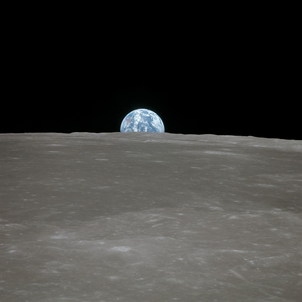 AS11-44-6548 - Apollo 11 - Apollo 11 Mission image - View of moon limb, with Earth on the horizon, Mare Smythii Region