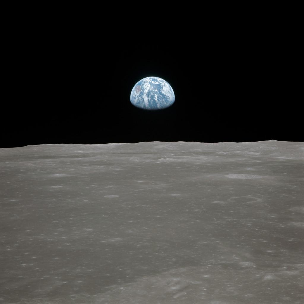 AS11-44-6553 - Apollo 11 - Apollo 11 Mission image - View of moon limb, with Earth on the horizon, Mare Smythii Region