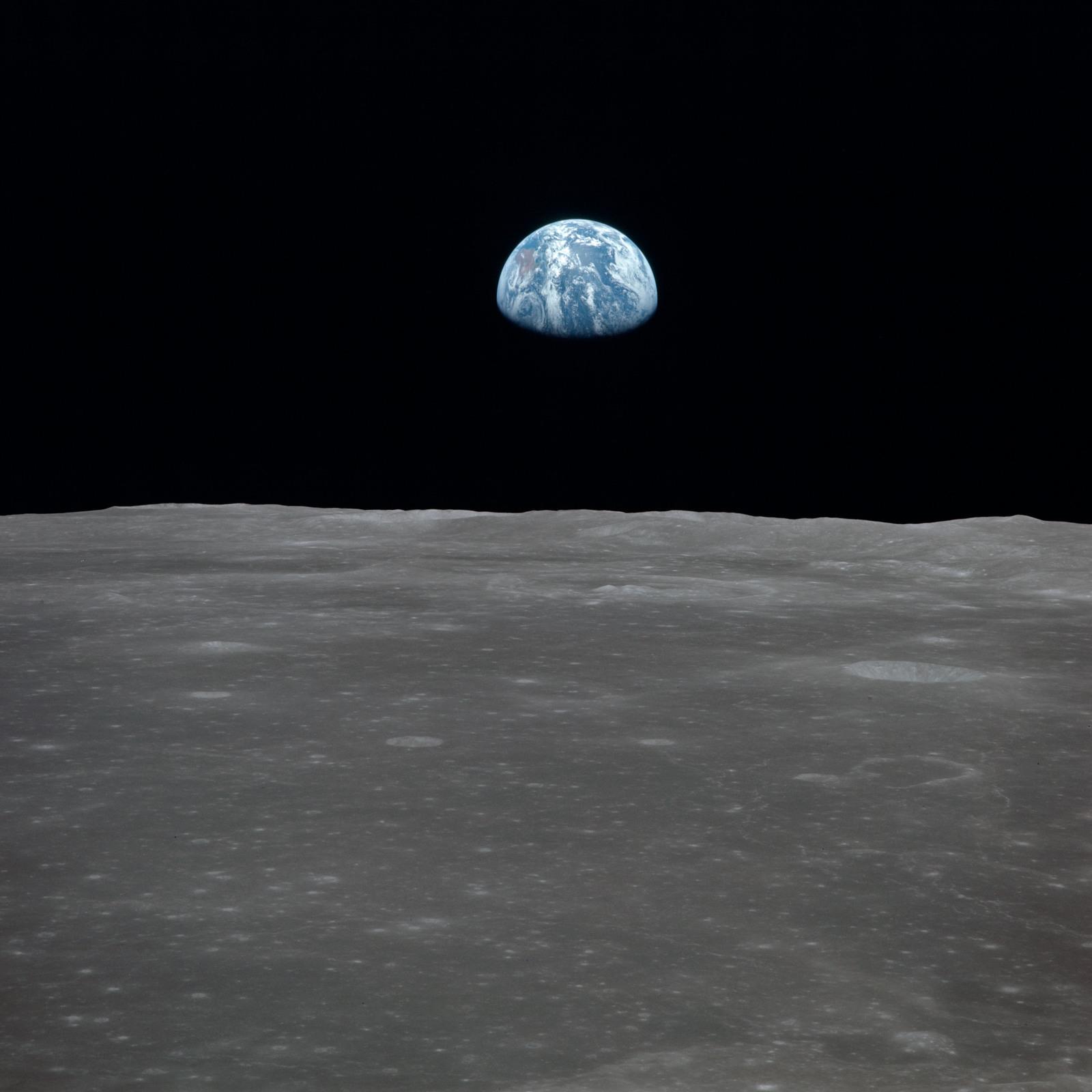 AS11-44-6556 - Apollo 11 - Apollo 11 Mission image - View of moon limb, with Earth on the horizon, Mare Smythii Region