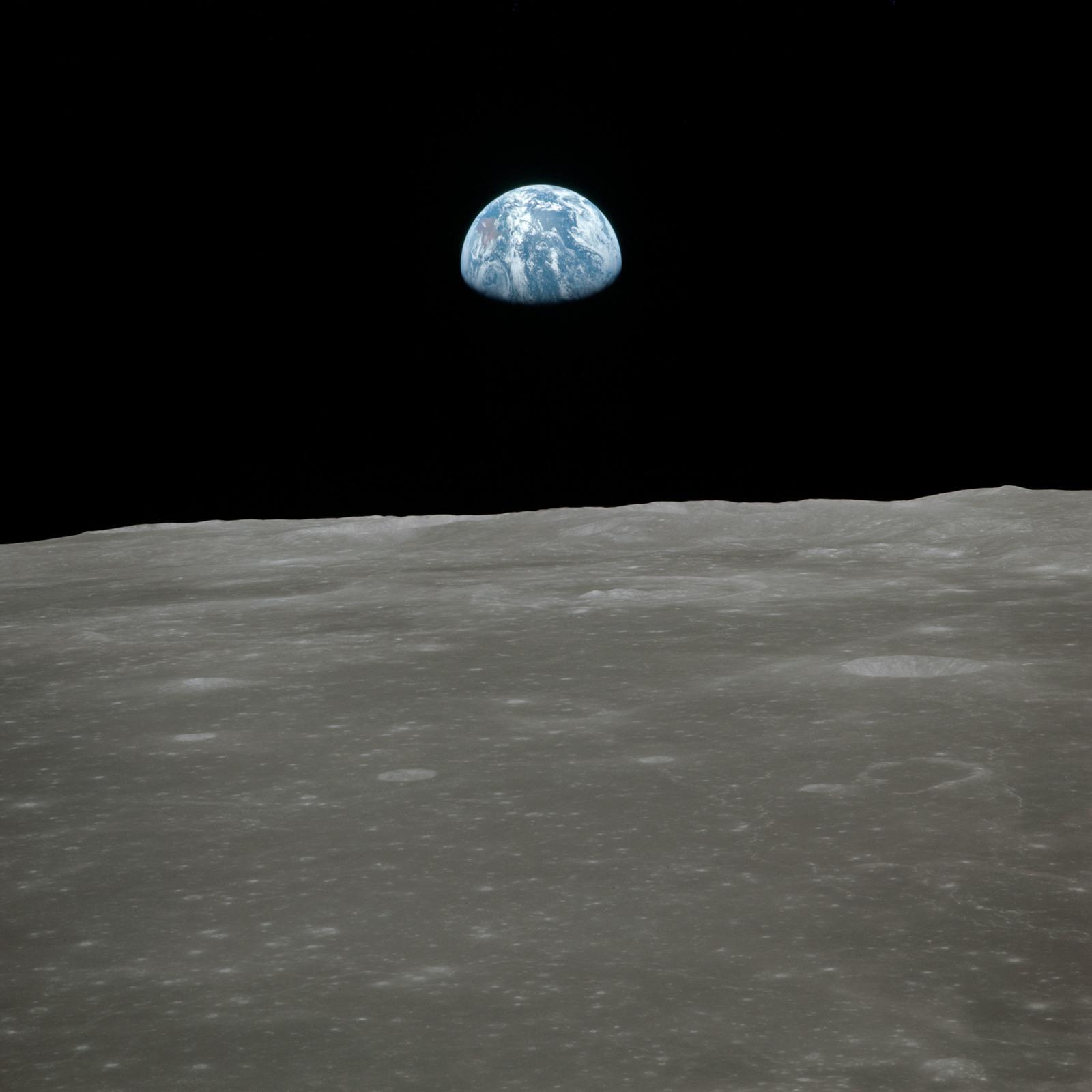 AS11-44-6557 - Apollo 11 - Apollo 11 Mission image - View of moon limb, with Earth on the horizon, Mare Smythii Region